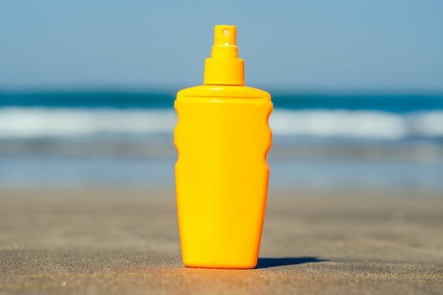 Botella de protector solar en el fondo de la playa en asia
