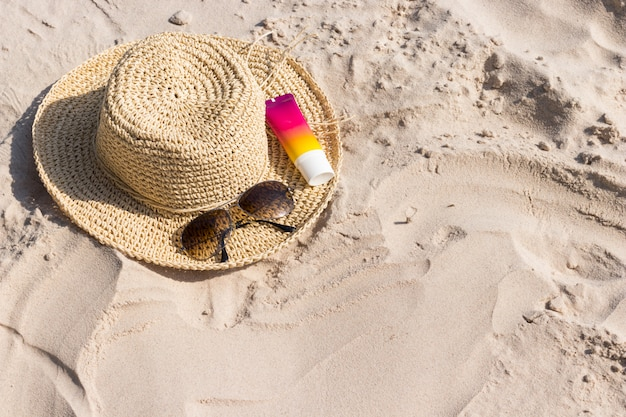 Botella de protector solar con gafas de sol y sombrero en la playa