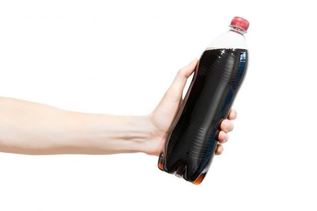 Botella de refresco gaseoso negro en la mano del ser humano.