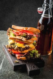 Botella con refresco y pila de sándwiches saludables con pan tostado, queso, carne, verduras y lechuga.