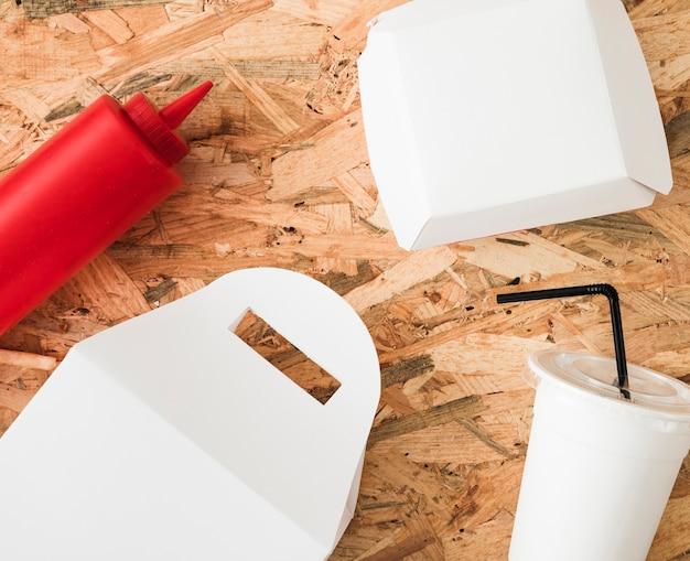 Botella de salsa; paquete blanco y bebida desechable sobre fondo de madera.