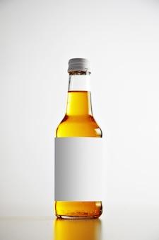 Botella sellada de vidrio transparente aislado sobre fondo simple con etiqueta blanca en blanco y bebida sabrosa en el interior