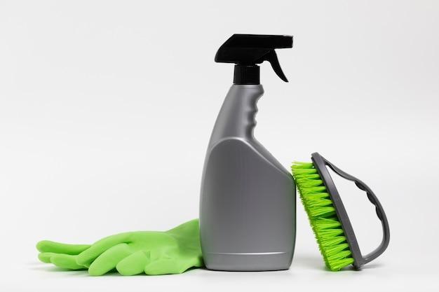 Botella de spray gris con guantes verdes y cepillo