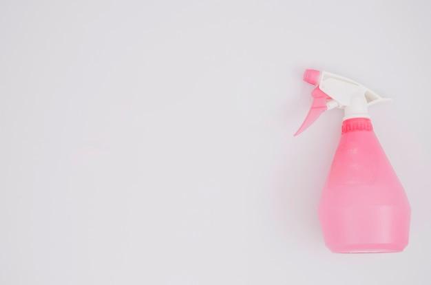 Botella de spray rosa sobre fondo blanco