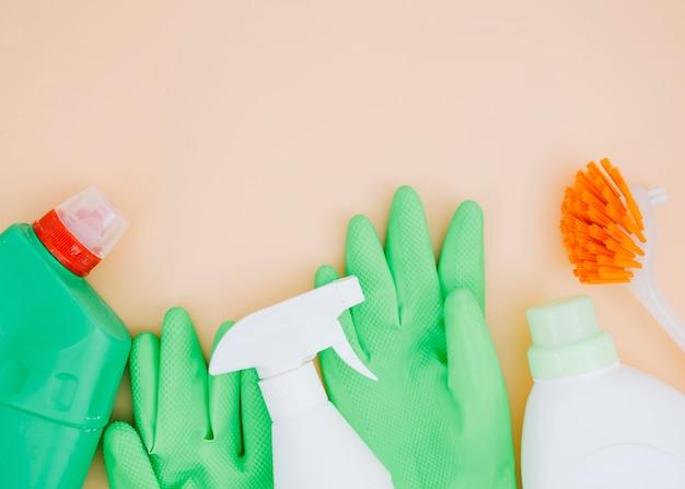 Botella de spray verde y guantes con detergente de limpieza con pincel sobre fondo beige