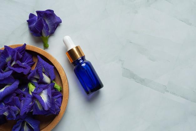 Botella de suero de aceite de flor de guisante de mariposa sobre fondo de mármol blanco
