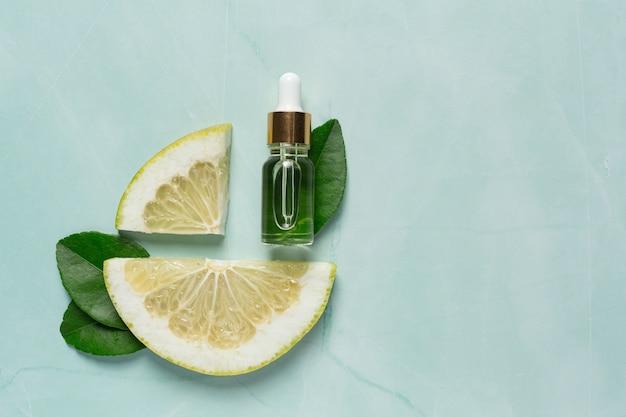 Botella de suero de aceite de pomelo puesta sobre fondo de luz verde