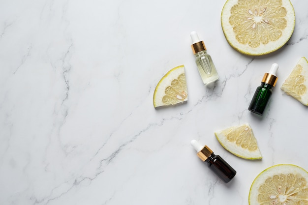 Botella de suero de aceite de pomelo puesta sobre fondo de mármol blanco