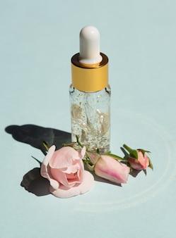 Botella de suero de oro de 24k sobre un fondo azul con flores color de rosa. el concepto de cuidado de la piel en casa.