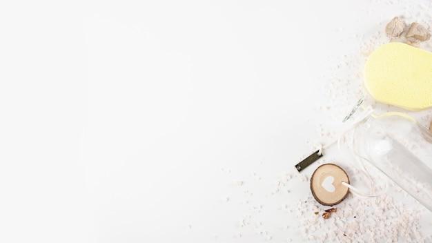 Una botella vacía con tapa en forma de corazón; esponja amarilla; spa piedra y sal de hierbas sobre fondo blanco