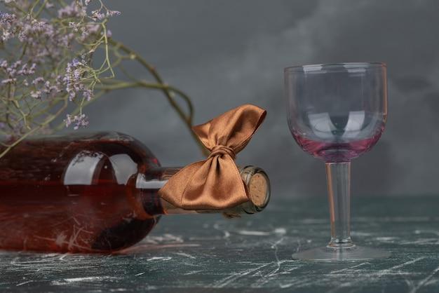 Botella vacía y vaso con flor marchita sobre superficie de mármol.