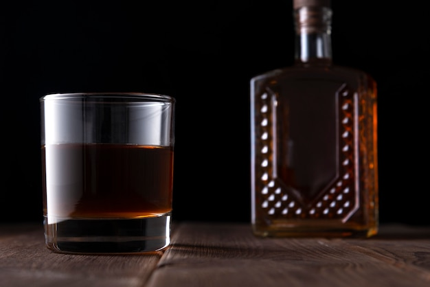 Botella y vaso con alcohol en una mesa de madera oscura