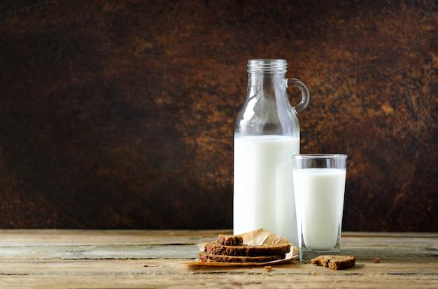 Botella y vaso de leche sobre fondo oscuro de madera.