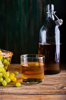 Botella y vaso en la mesa con jugo de uvas frescas
