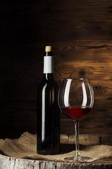 Botella y vaso de vino tinto en barril de madera con fondo de madera oscura