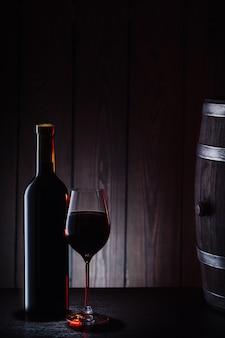 Botella y vaso de vino tinto contra barriles y tablas.