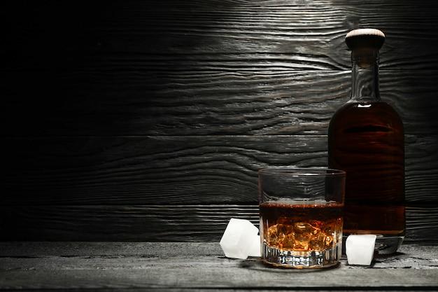 Botella y vaso de whisky y cubitos de hielo sobre fondo de madera, espacio para texto
