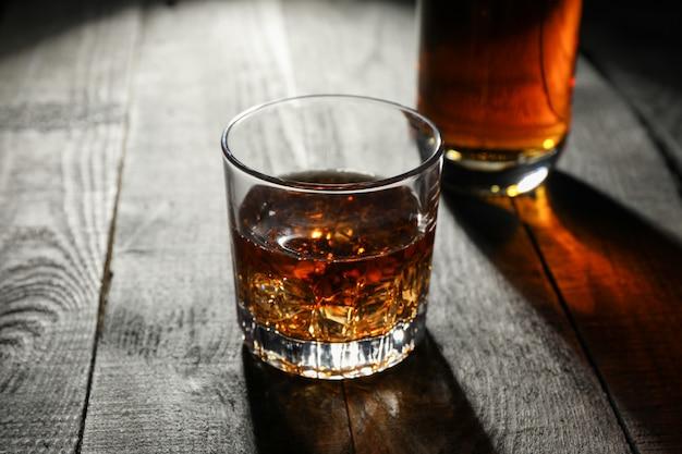 Botella y vaso de whisky sobre fondo de madera, espacio para texto