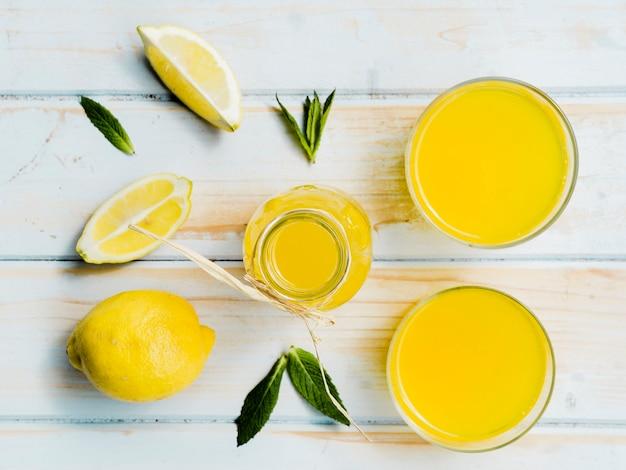 Botella y vasos de bebida amarilla con limón fresco y menta.
