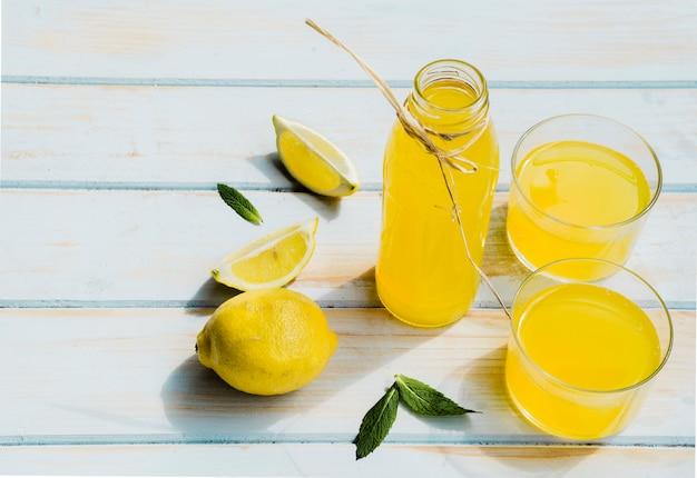 Botella y vasos con cóctel de limón en la mesa de madera shabby