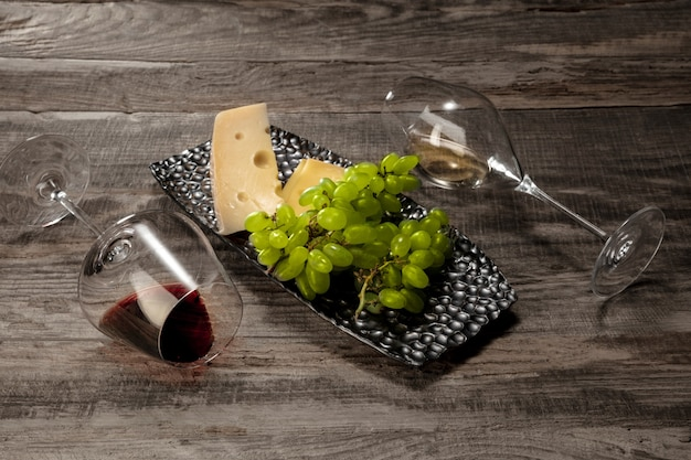 Una botella y vasos de vino tinto y blanco con frutas.