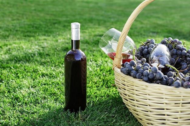 Botella y vasos de vino tinto y canasta de uva fresca