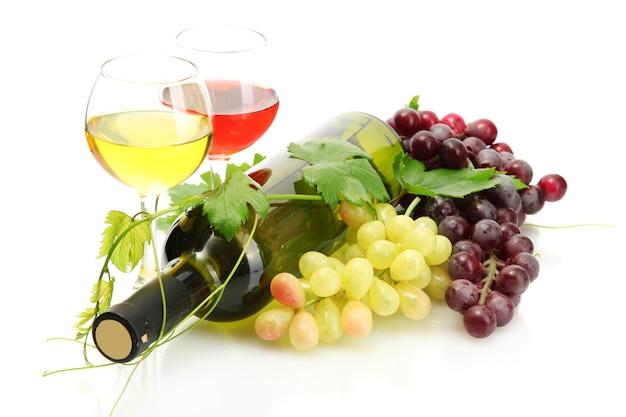Botella y vasos de vino y uvas maduras aislado en blanco
