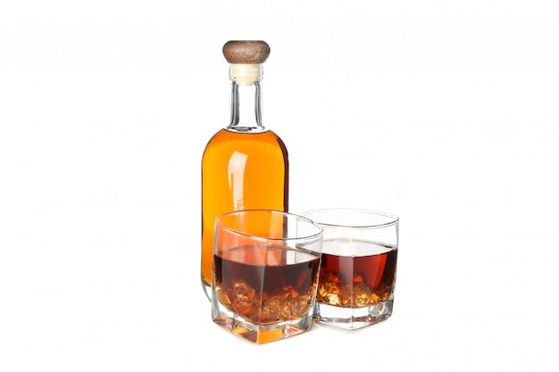 Botella y vasos con whisky aislado sobre fondo blanco.