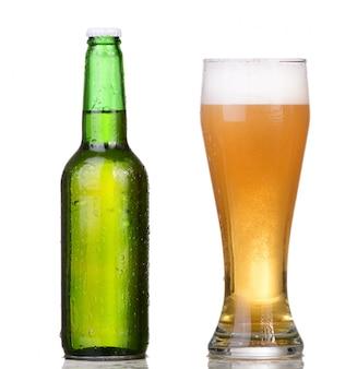 Botella verde refrigerada con condensado y un vaso de cerveza sobre fondo blanco aislado