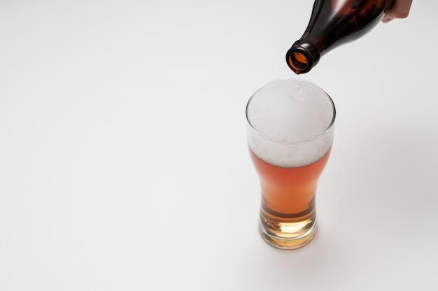 Botella vertiendo cerveza en vidrio con espacio de copia