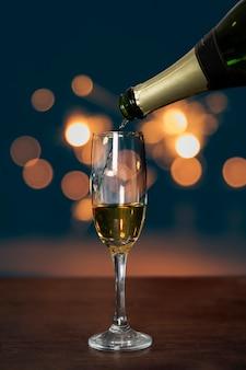 Botella vertiendo champán en vaso