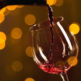 Botella vertiendo vino tinto en vaso con efecto bokeh