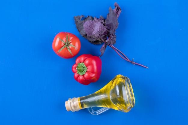 Botella de vidrio de aceite virgen extra con albahaca, pimiento rojo y tomate sobre mesa azul.