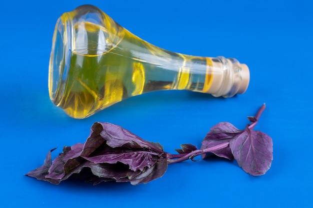 Botella de vidrio de aceite virgen extra y albahaca sobre superficie azul.