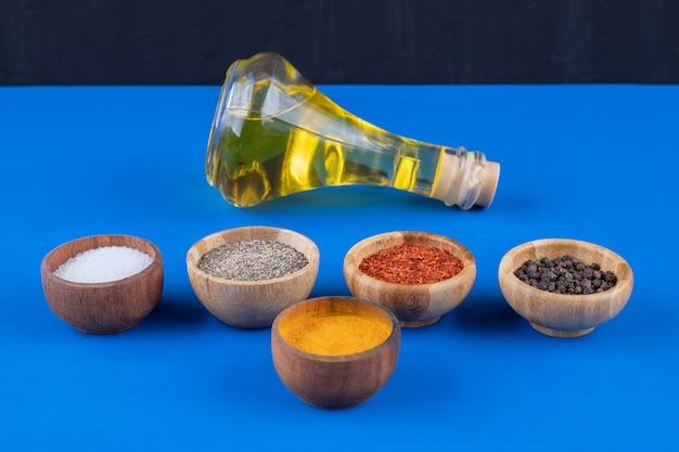 Botella de vidrio de aceite virgen extra y diversas especias sobre superficie azul