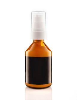 Botella de vidrio ámbar cosmético oscuro con dispensador aislado en la pared blanca.
