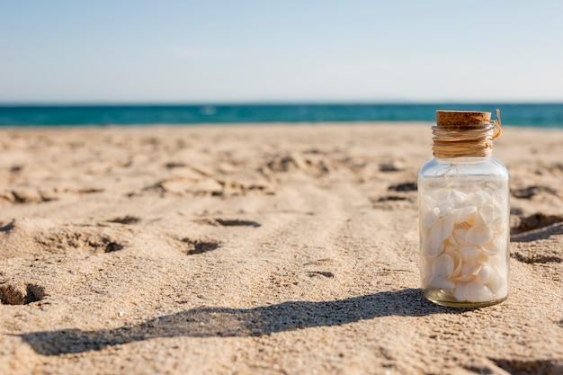 Botella de vidrio con conchas en la arena