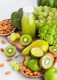 Botella de vidrio de jugo de batido fresco frutas y verduras en tonos verdes orgánicos en la cocina de piedra. con nueces almendras en un tazón.