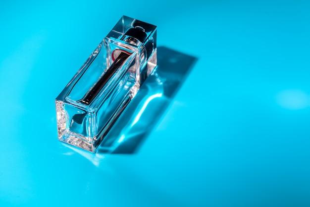 Botella de vidrio de perfume sobre fondo azul claro.