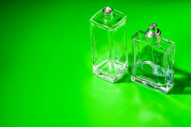 Botella de vidrio de perfume sobre fondo verde claro.