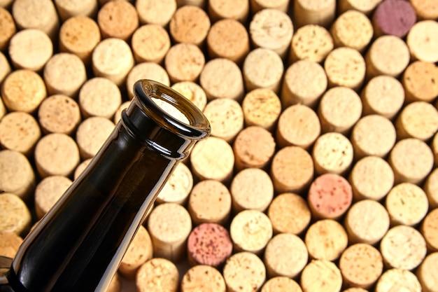 Botella de vidrio tapado con corcho de vino tinto sobre fondo de corchos de botellas usadas