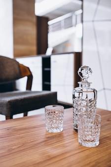 Botella de vidrio vacía con dos vasos en una mesa de madera