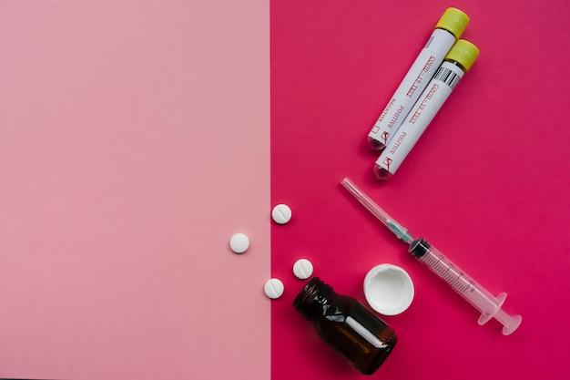 Botella de vidrio vacía con pastillas, dos pruebas de coronavirus positivas y jeringas. concepto de fondo minimalista rosa y rojo