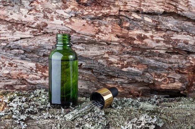 Una botella de vidrio verde y una pipeta con suero, aceite esencial sobre fondo de musgo verde y corteza de árbol.
