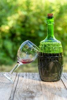 Botella de vidrio con vino tinto y una copa. al aire libre.