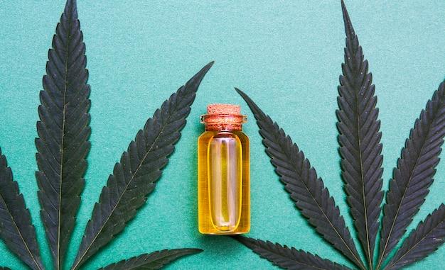 Botella de vidrio de vista superior con aceite de cannabis cerca de la planta