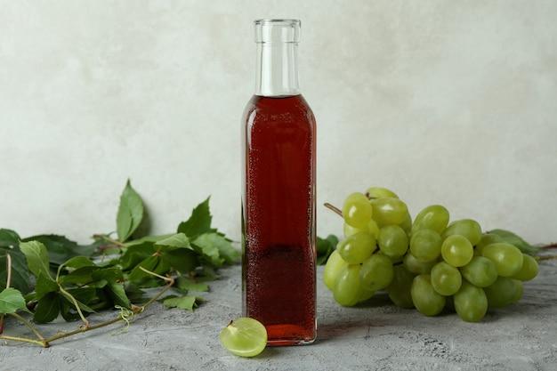 Botella de vinagre, uva y hojas sobre tabla con textura gris
