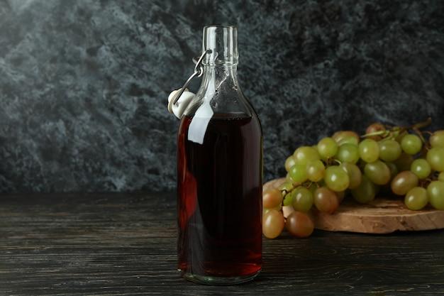 Botella de vinagre y uva sobre mesa de madera rústica