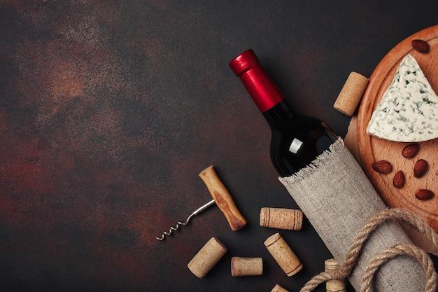 Botella de vino, almendras, sacacorchos y corchos, vista superior.