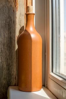 Botella de vino de barro, se encuentra en el alféizar de la ventana